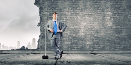 cement solution: Young determined businessman with big hammer in hands
