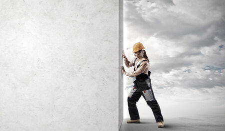 Strong man in uniform and helmet pushing wall  Place for text photo