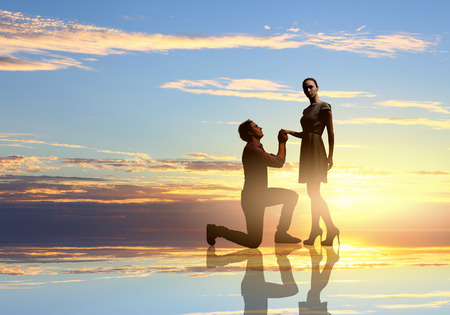Silhouettes of man making proposal to woman Stock Photo
