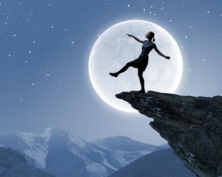 Silhouet van de vrouw lopen op de rand van de rots