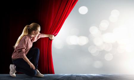 カジュアルなオープニングの赤いカーテンの若い女性