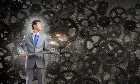 Young determined businessman with wrench in hands and cogwheels at background Stock Photo - 30537092