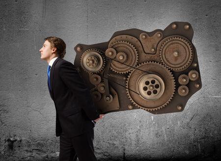 Young businessman carrying cogwheel mechanism on back Stock Photo - 30537097