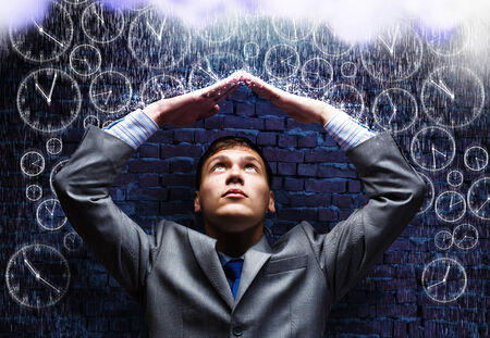 Young businessman under rain covering head with hands photo
