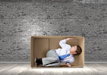 Young frustrated businessman trapped in small carton box Stock Photo - 30537109