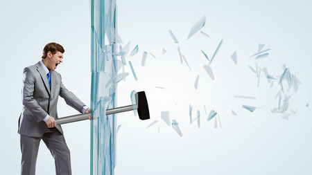 Young determined businessman breaking glass with hammer photo