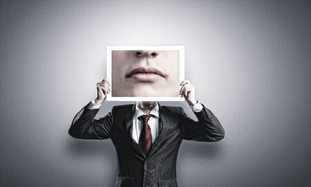 Businessman hiding head behind photo with huge mouth photo