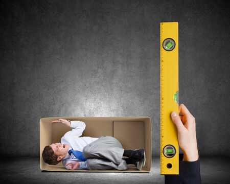 Close up of business person hand measuring man in carton box photo