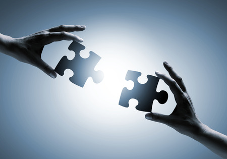 linking together: Close up image of hands connecting puzzle elements