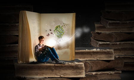 Teenager boy wearing jeans and shirt and reading book photo