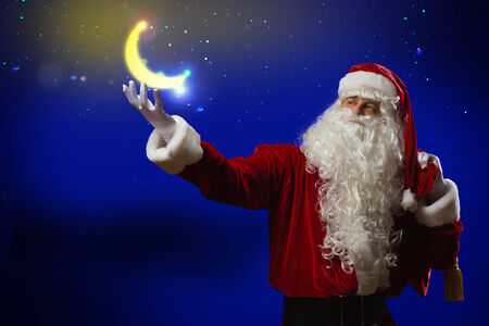 Santa Claus holding shining moon in palm photo