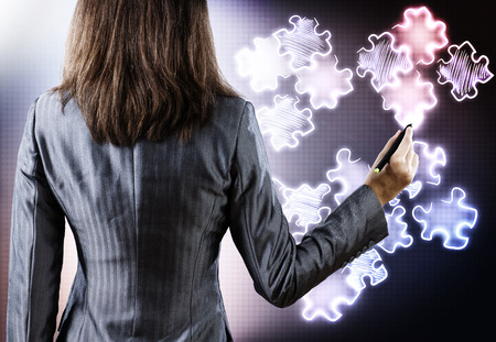 Rear view of businesswoman drawing puzzle elements photo