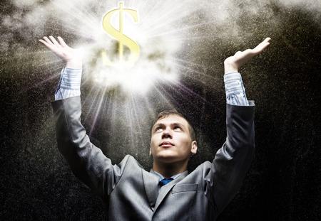 Businessman looking at shining dollar symbol above