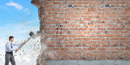 cement solution: Young businessman breaking old wall with hammer