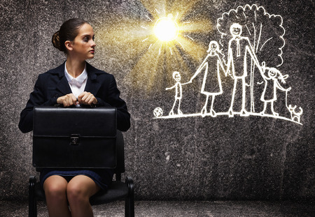 work life balance: Young upset businesswoman sitting on chair with briefcase