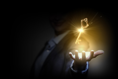 Close up image of business person holding shining key