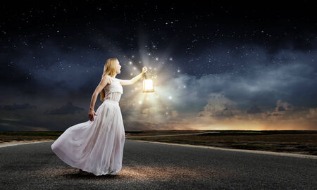 magical equipment: Young woman in white long dress with lantern Stock Photo