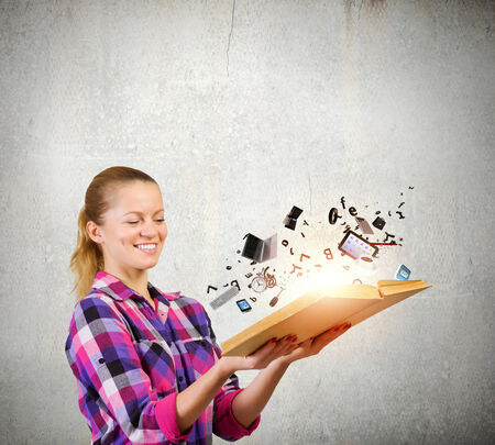 Young woman in casual holding opened book with icons flying out photo