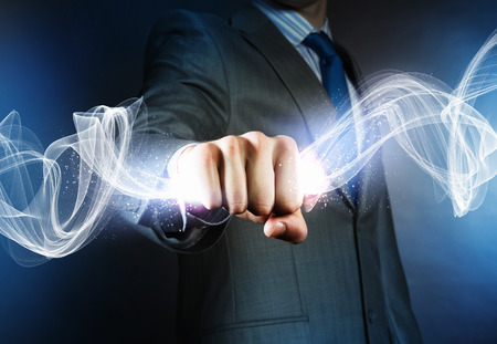 supernatural power: Close up of businessman hand holding light ray in fist Stock Photo