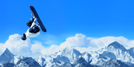 Snowboarder making high jump in clear blue sky Stock Photo
