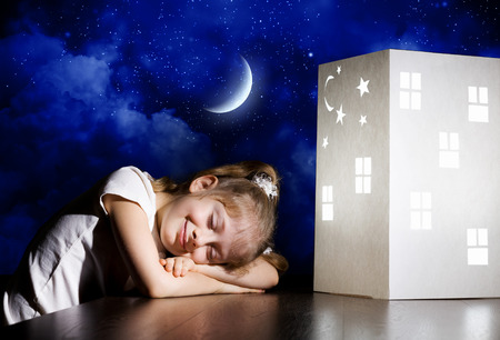 Cute little girl sleeping near model of house and dreaming photo