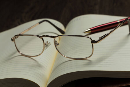 Eye glasses lying on opened blank notepad photo