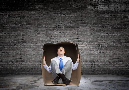 unsatisfied: Young frustrated businessman trapped in small carton box