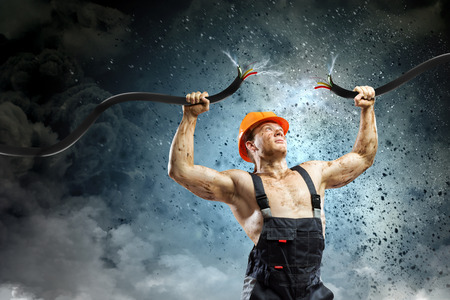 electrocute: Strong man in uniform tearing electricity cable with hands Stock Photo