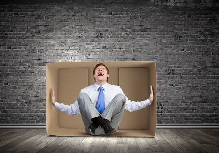 unsatisfied: Young frustrated businessman sitting in small carton box Stock Photo