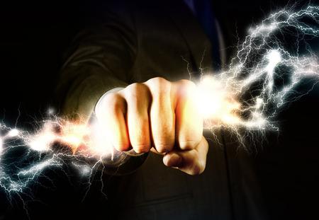 拳に雷を持っているビジネスマン手のクローズ アップ 写真素材
