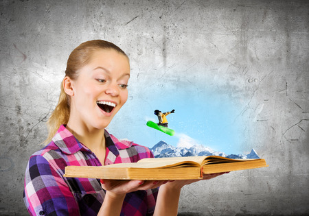 Young woman looking in opened book and snowboarder making jump photo