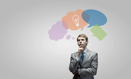 Young thoughtful businessman and colorful speech bubbles above photo