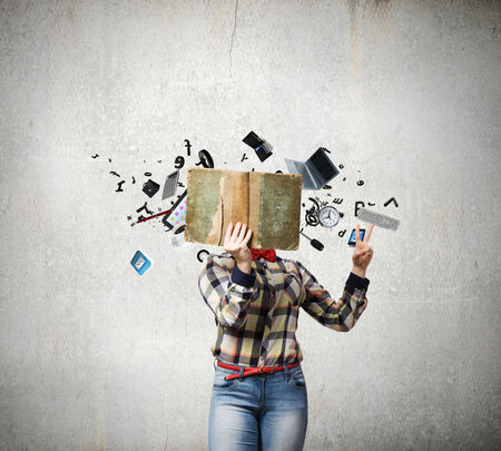 adult learning: Woman in casual wear hiding her face behind book