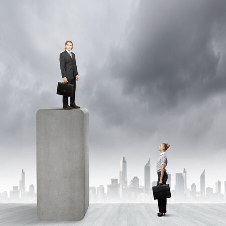 Conceptual image of businesswoman looking at man standing on bar photo
