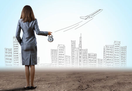 corporate airplane: Rear view of businesswoman holding old alarm clock