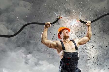 electrifying: Strong man in uniform tearing electricity cable with hands Stock Photo