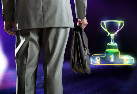Rear view of businessman with briefcase and podium with cup photo