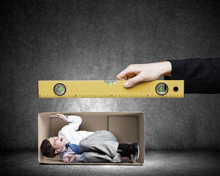 claustrophobia: Close up of business person hand measuring man in carton box