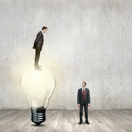 Businessman standing on top of light bulb and looking down photo