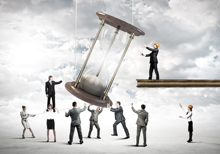 Conceptual image of business people looking at sandglass photo