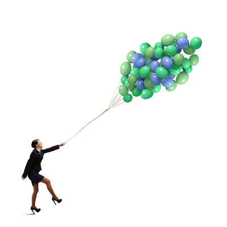 achievement concept: Young joyful businesswoman walking with bunch of colorful balloons Stock Photo