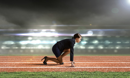 start position: Side view of businesswoman at stadium standing in start position