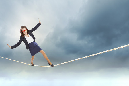 Young attractive businesswoman balancing on rope high in sky