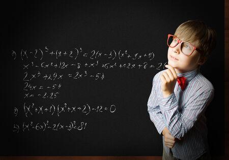 Smart boy in red glasses near blackboard with formulas photo