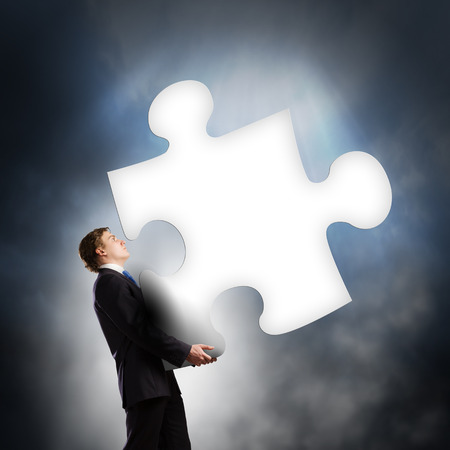Young businessman carrying big puzzle in hands photo