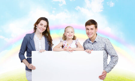 Happy family of three holding white blank banner  Place for text photo