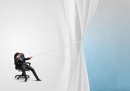 Young businessman sitting in chair and pulling curtain with rope photo
