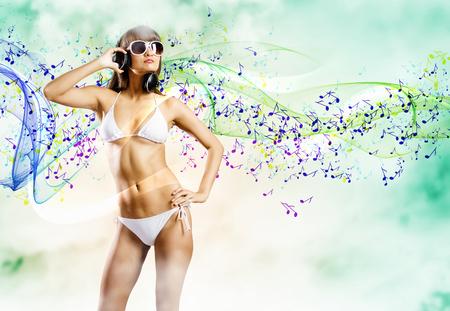 Young pretty girl in white bikini and headphones photo