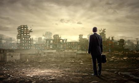 Achteraanzicht van zakenman kijken naar de ruïnes van de stad