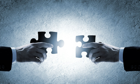 Close up image of hands connecting puzzle elements photo